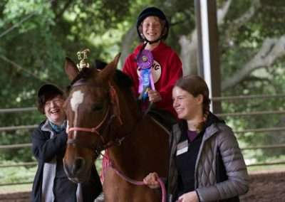 Elementary age child riding horse with purple ribbon led by two smiling adults