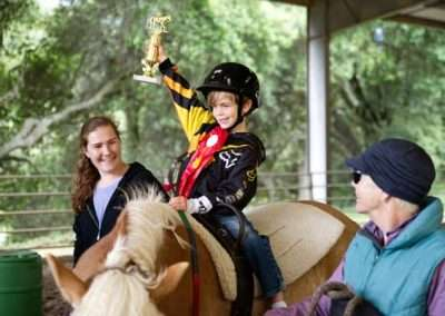 Young boy smiling on horse holds arm up showing trophy