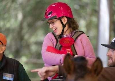 Smiling girl wearing pink receives red ribbon