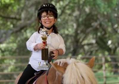 Smiling girl receive trophy riding horse