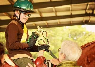 Smiling elementary age child on horse receives trophy
