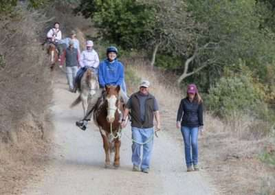Group of smiling people outside leading riders on horses