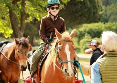 Young person with a green helmet being led on a Palamino horse