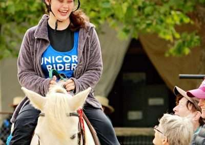 Smiling girl in a blue helmet sitting on a white horse