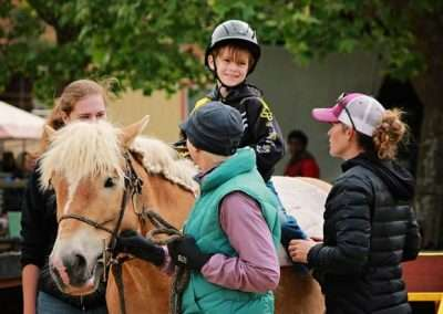 Young child on horse sitting with smiling adults