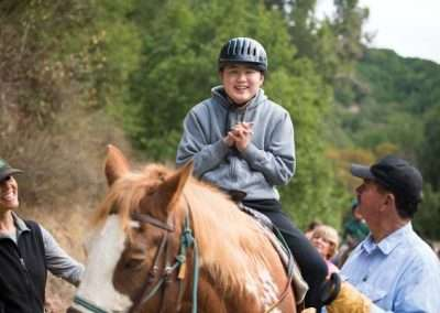 Young person being led by people riding a horse