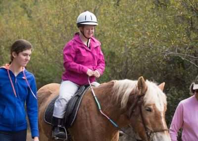 Girl in pink being led riding a Palamino horse