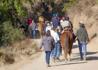 From the back, people lead a group of riders on a path