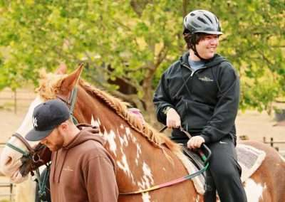 Detail of smiling young person on a American Paint horse being led by assistant