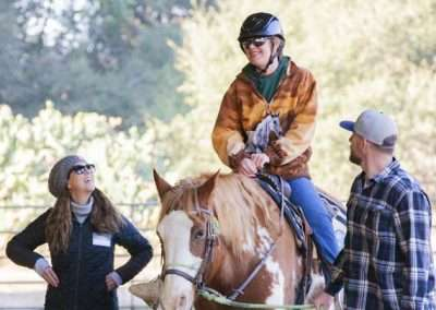 Young person riding a American Paint horse and being led by smiling assistants