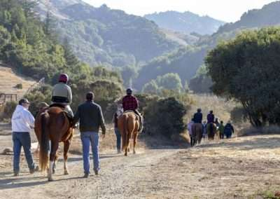 From the back, riders go down a dirt path being led by assistants