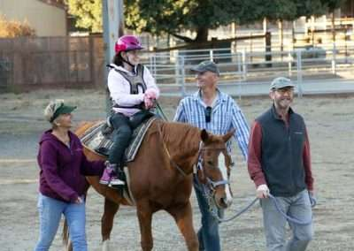 Smiling adults walk with horse and rider