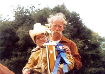 Historic photo on a boy holding a blue ribbon