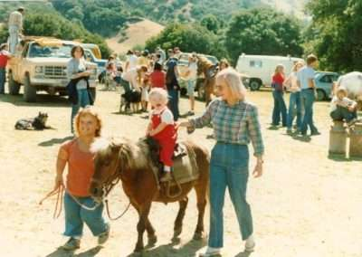 Historical photo of baby on pony being led by two people